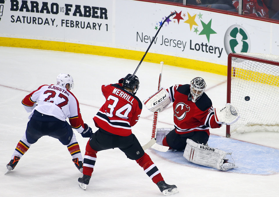 Photo - Florida Panthers' Nick Bjugstad (27) shots the puck past New Jersey Devils' Jon Merrill (34) and goalie Cory Schneider (35) for a goal during the second period of an NHL hockey game in Newark, N.J., Saturday, Jan. 11, 2014. (AP Photo/Rich Schultz)