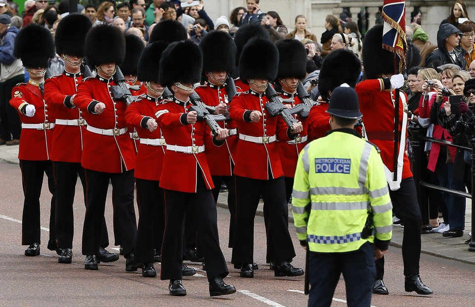 Photo - A police officer keeps guard as British soldiers march along The Mall in London, Thursday, May 23, 2013. Britain was coming to terms with an apparent return of terrorism to its capital Thursday as new information emerged about the butchering of a British soldier near an army barracks in Woolwich by suspected Islamic radicals.  (AP Photo/Kirsty Wigglesworth)