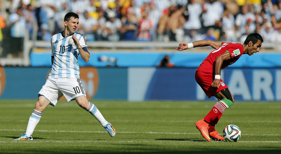 Photo - Argentina's Lionel Messi, left, watches as Iran's Mehrdad Pooladi takes the ball away from him during the group F World Cup soccer match between Argentina and Iran at the Mineirao Stadium in Belo Horizonte, Brazil, Saturday, June 21, 2014. (AP Photo/Victor R. Caivano)