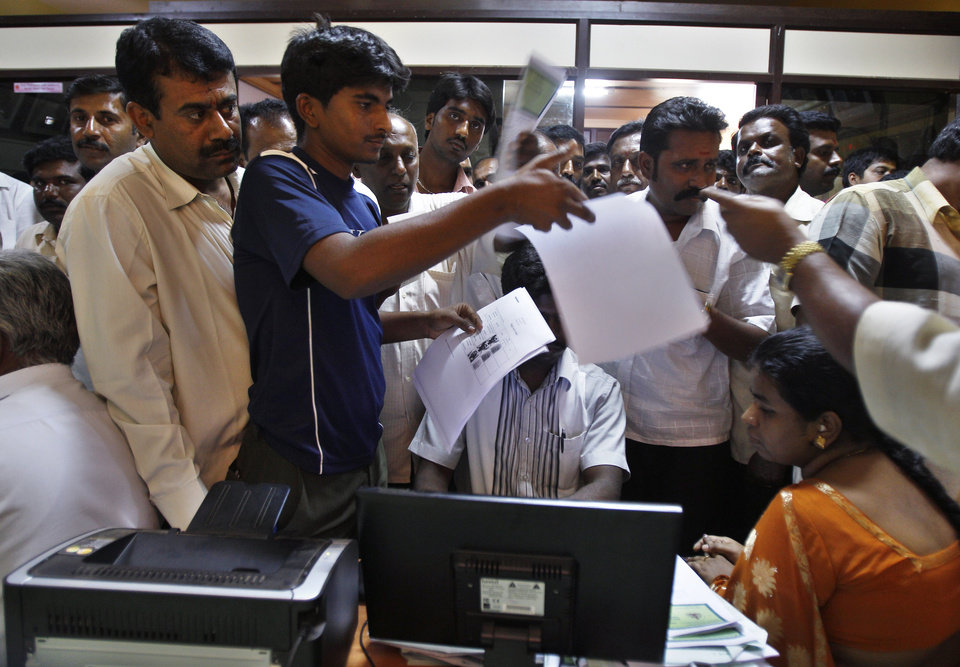 Photo - In this Dec. 10, 2012 photo, people crowd inside the government registrar's office to get their land registered, in Hoskote 30 kilometers (19 miles) from Bangalore in the southern Indian state of Karnataka. For years, Karnataka's land records were a quagmire of disputed, forged documents maintained by thousands of tyrannical bureaucrats who demanded bribes to do their jobs. In 2002, there were hopes that this was about to change. (AP Photo/Aijaz Rahi)
