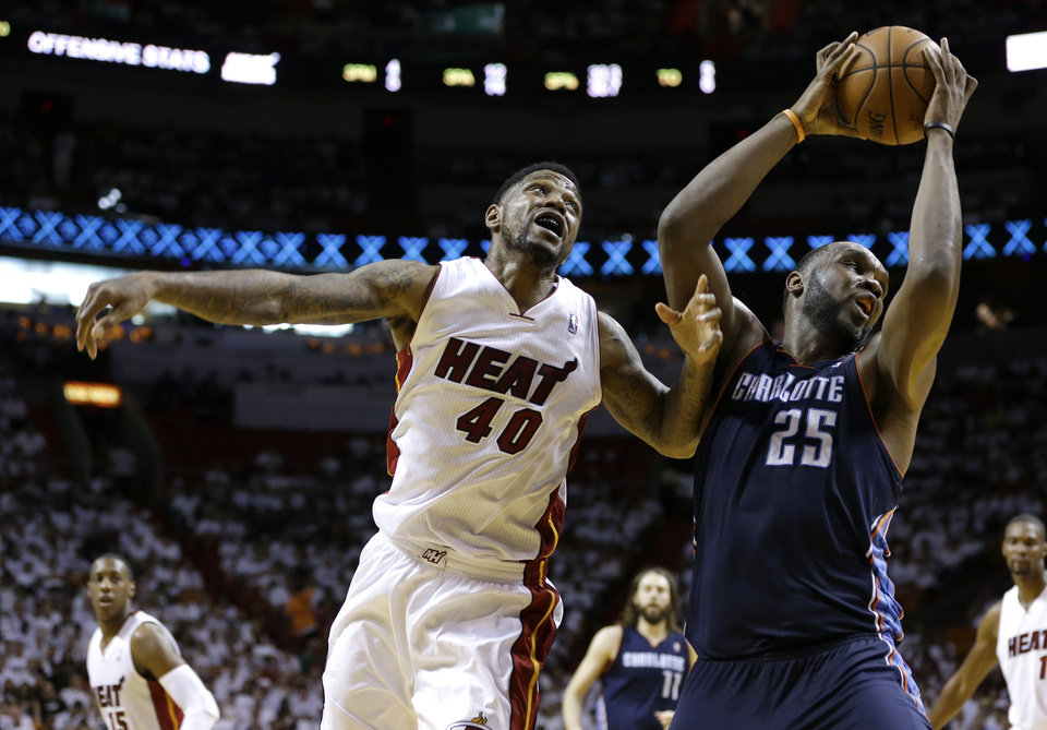 Photo - Charlotte Bobcats' Al Jefferson (25) takes a pass from a teammate over Miami Heat's Udonis Haslem (40) during the second half in Game 1 of an opening-round NBA basketball playoff series on Sunday, April 20, 2014, in Miami. The Heat defeated the Bobcats 99-88. (AP Photo/Lynne Sladky)