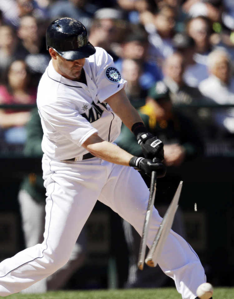 Photo - Seattle Mariners' Willie Bloomquist splits his bat as he grounds out against the Oakland Athletics in the third inning of a baseball game Sunday, April 13, 2014, in Seattle. (AP Photo/Elaine Thompson)