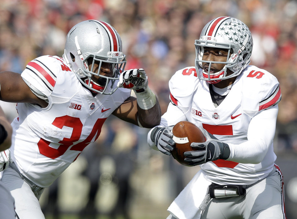 Photo - Ohio State quarterback Braxton Miller, right, fakes a hand off to running back Carlos Hyde during the first half of an NCAA college football game in West Lafayette, Ind., Saturday, Nov. 2, 2013. (AP Photo/Michael Conroy)