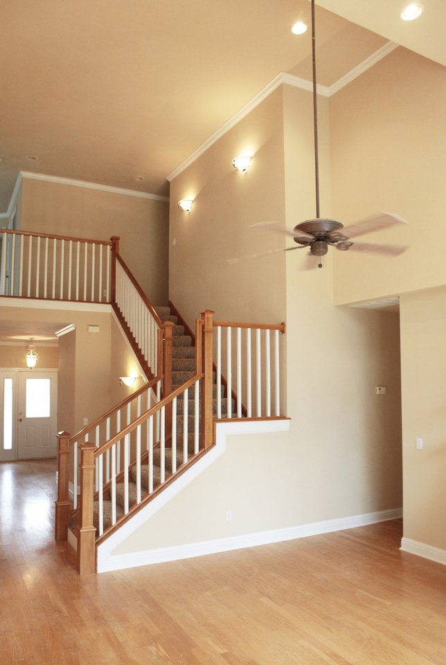 The stairs and ceiling fan accentuate the ceiling height of the living area of the home at 8012 NE 140. Photo by David McDaniel, The Oklahoman