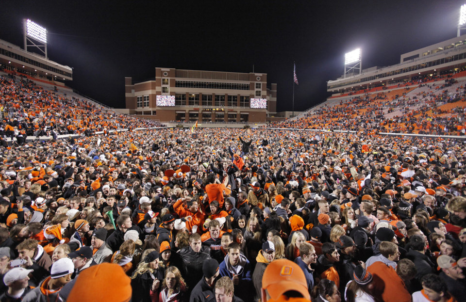 Photo - Fans celebrate the 44-10 win over the Sooners during the Bedlam college football game between the Oklahoma State University Cowboys (OSU) and the University of Oklahoma Sooners (OU) at Boone Pickens Stadium in Stillwater, Okla., Saturday, Dec. 3, 2011. Photo by Chris Landsberger, The Oklahoman