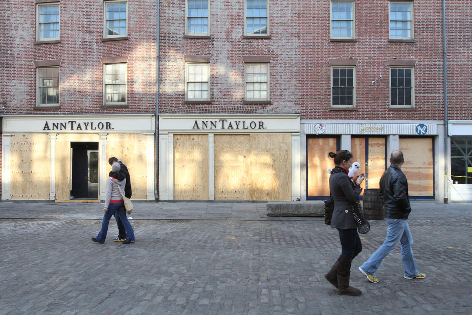 Photo -   In this Friday, Nov. 23, 2012 photo, people walk past boarded up shops at New York's South Street Seaport. The South Street Seaport, a popular tourist destination, remains a ghost town since Superstorm Sandy. (AP Photo/Tina Fineberg)