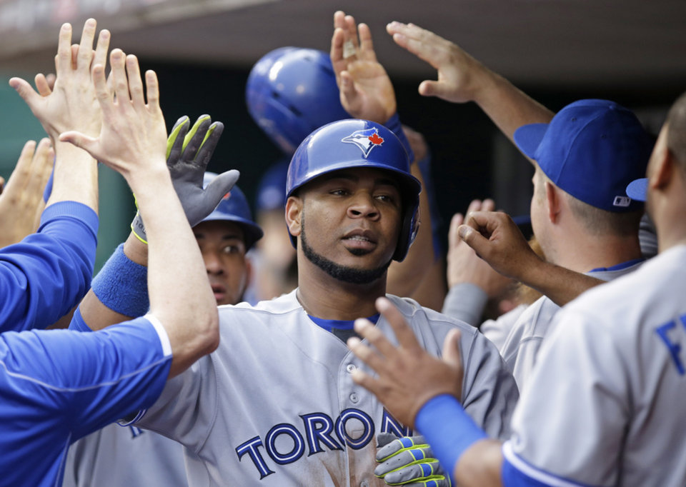 Photo - Toronto Blue Jays' Edwin Encarnacion is congratulated in the dugout after hitting a three-run home run off Cincinnati Reds starting pitcher Mat Latos in the third inning of a baseball game, Friday, June 20, 2014, in Cincinnati. (AP Photo/Al Behrman)