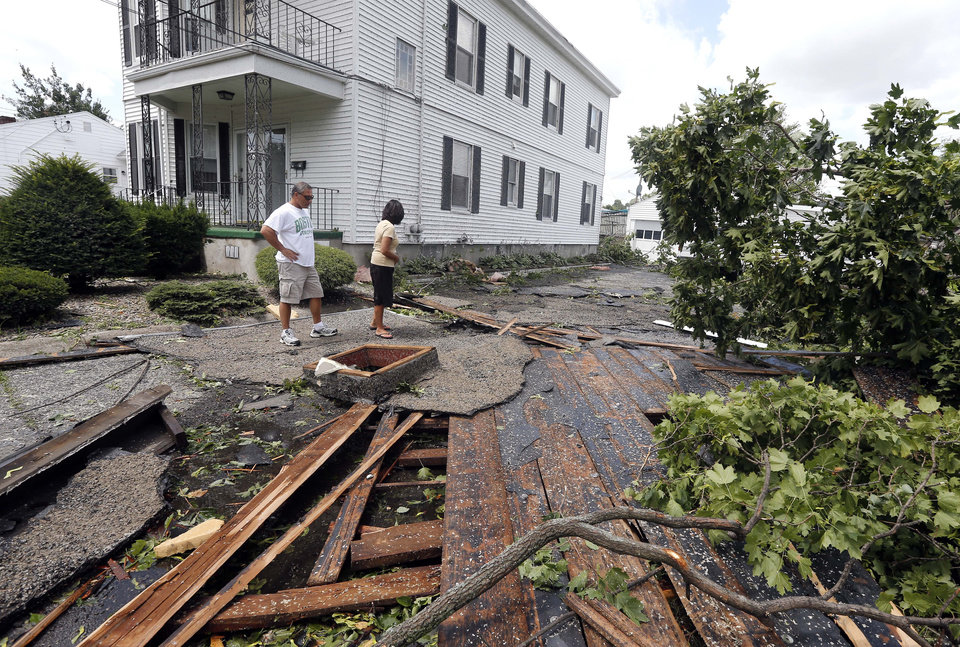 Photo - Christine Molle and her husband, Wayne, survey the damage to her mother's house in Revere, Mass., Monday, July 28, 2014, after a tornado touched down. Revere Deputy Fire Chief Mike Viviano says the fire department in the coastal city has received dozens of calls reporting partial building and roof collapses, and downed trees and power lines. Viviano says there are no immediate reports of deaths or serious injuries. (AP Photo/Elise Amendola)