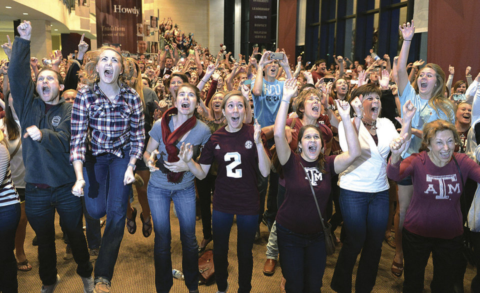 Photo - FILE - In this Dec. 8, 2012 file photo, Texas A&M students and fans celebrate on the campus in College Station, Texas, after the Heisman Trophy was awarded to A&M quarterback Johnny Manziel in New York. (AP Photo/Bryan-College Station Eagle, Dave McDermand)