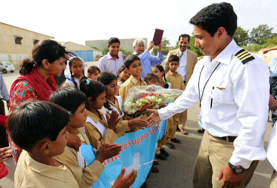 Photo - In this July 2014 photo provided by The Citizens Foundation 17-year-old Haris Suleman is greeted by students from the Citizens Foundation school in Lahore, Pakistan, during his around-the-world flight. The body of the Plainfield, Indiana, teen was recovered after his single-engine plane crashed Tuesday, July 22, 2014 shortly after taking off from Pago Pago in American Samoa. Crews were still searching for his father, 58-year-old Babar Suleman, who was flying with him. (AP Photo/Courtesy The Citizens Foundation)