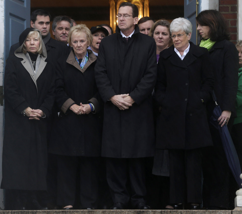 Photo - Connecticut Gov. Dan Malloy, center, stands with other officials to observe a moment of silence while bells ring 26 times in Newtown, Conn., Friday, Dec. 21, 2012, in honor of the victims who were killed last Friday during the shooting at Sandy Hook Elementary School. (AP Photo/Seth Wenig)
