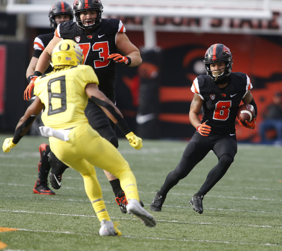 Photo - Oregon State wide receiver Trevon Bradford (8) tries to get past Oregon safety Jevon Holland (8) in the first half of an NCAA college football game in Corvallis, Ore., on Friday, Nov. 23, 2018. (AP Photo/Timothy J. Gonzalez)