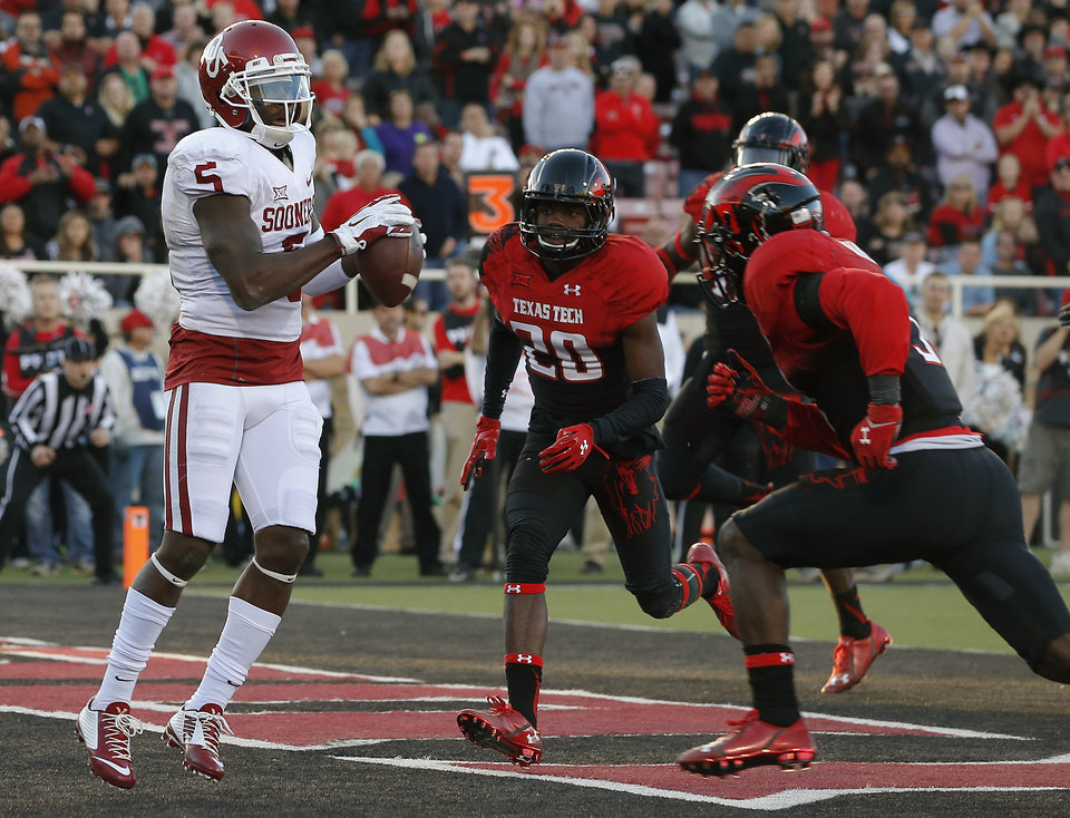 Photo - Oklahoma's Durron Neal (5) catches a touchdown pass in front of Texas Tech's Tevin Madison (20) during a college football game between the University of Oklahoma Sooners (OU) and the Texas Tech Red Raiders at Jones AT&T Stadium in Lubbock, Texas, Saturday, November 15, 2014.  Photo by Bryan Terry, The Oklahoman