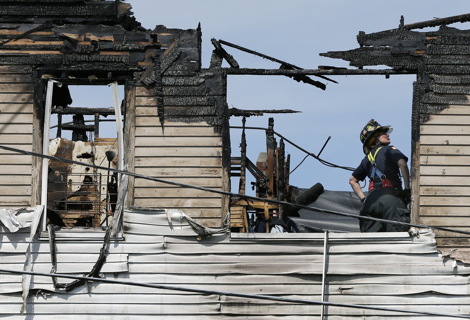 Photo - A firefighter works on the top floor inside a burned three-story apartment and business building in Lowell, Mass., Thursday, July 10, 2014, where officials said seven people died in a fast-moving pre-dawn blaze. The victims' names were not immediately made public.  The cause and origin of the blaze remain under investigation, State Fire Marshal Stephen Coan said.  (AP Photo/Elise Amendola)