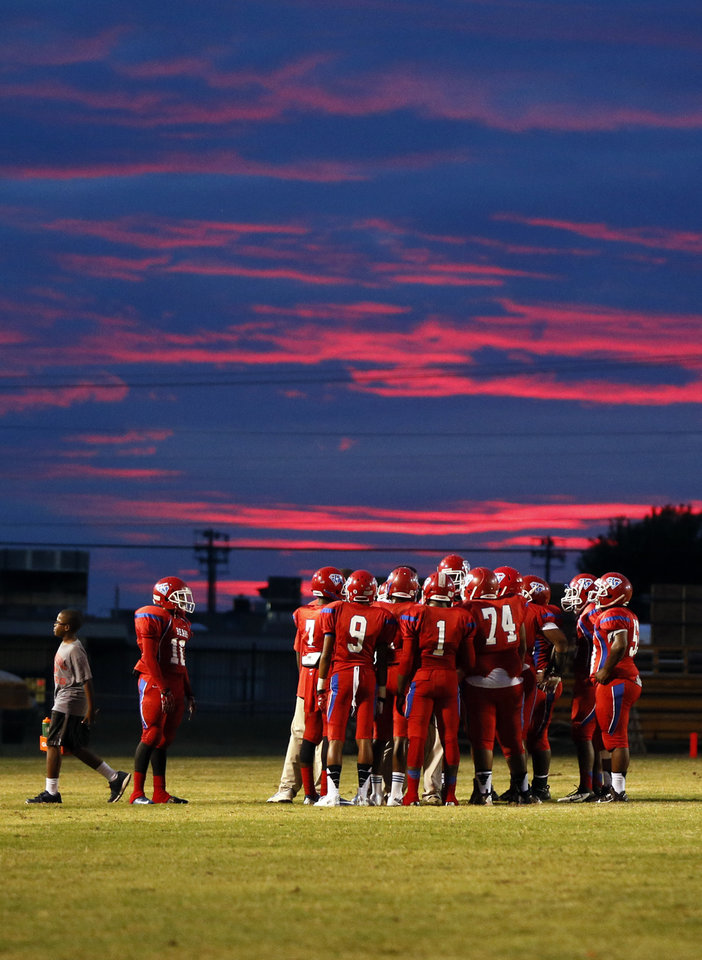 The sun sets behind John Marshall players during a high school football game between John Marshall and Crooked Oak at Star Spencer's Carl Twidwell Stadium, 3001 NE Spencer Rd., in Spencer, Okla., Thursday, Sept. 19, 2013. Photo by Nate Billings, The Oklahoman