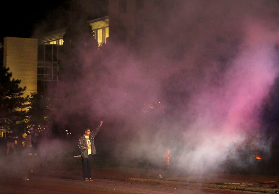 Photo - A protester holds their hand in the air tear gas goes in the air in front of the Oklahoma City Police Department in Oklahoma City, Sunday, May 31, 2020. The protest was in response to the death of George Floyd. [Sarah Phipps/The Oklahoman]