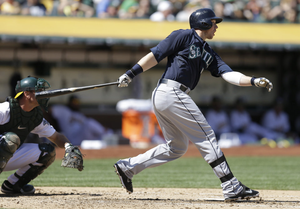 Photo - Seattle Mariners' Justin Smoak follows through on his RBI single off Oakland Athletics' Sonny Gray in the third inning of an MLB American League baseball game Sunday, April 6, 2014, in Oakland, Calif. (AP Photo/Ben Margot)