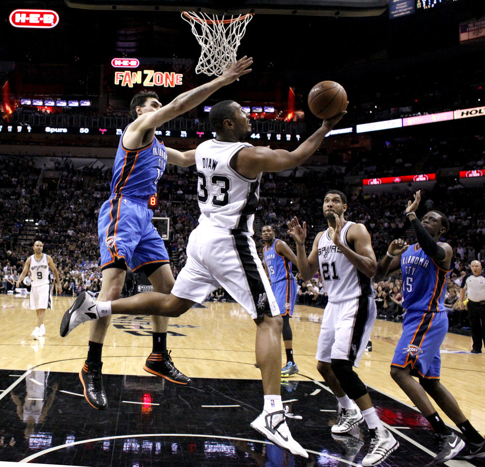Photo - San Antonio's Boris Diaw (33) shoots a lay up as Oklahoma City's Steven Adams (12) defends during Game 2 of the Western Conference Finals in the NBA playoffs between the Oklahoma City Thunder and the San Antonio Spurs at the AT&T Center in San Antonio, Wednesday, May 21, 2014. Photo by Sarah Phipps