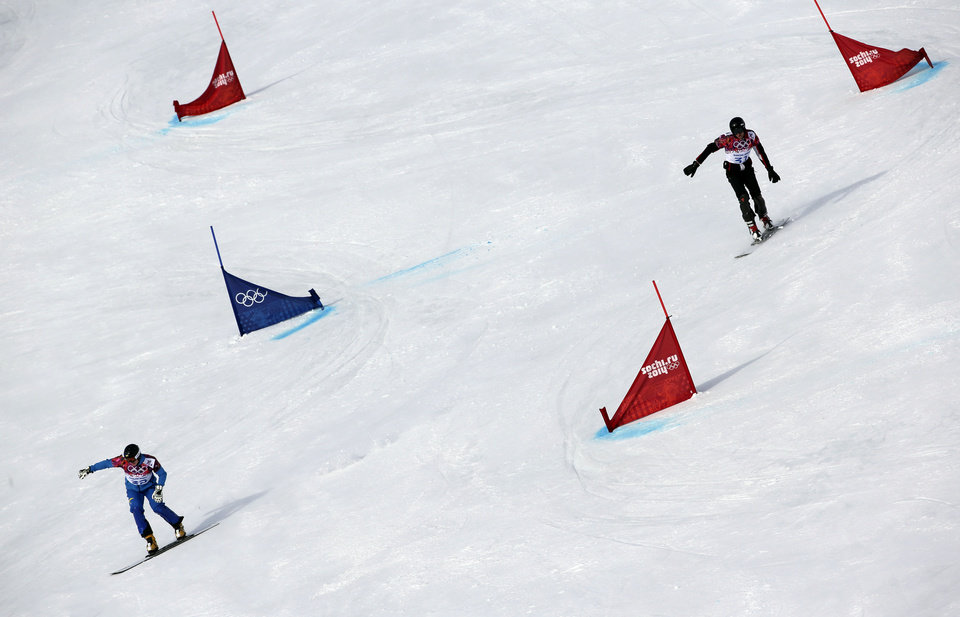 Photo - Ukraine's Yosyf Penyak, left, competes against Bulgaria's Radoslav Yankov during men's snowboard parallel giant slalom qualifying at the Rosa Khutor Extreme Park, at the 2014 Winter Olympics, Wednesday, Feb. 19, 2014, in Krasnaya Polyana, Russia. (AP Photo/Andy Wong)