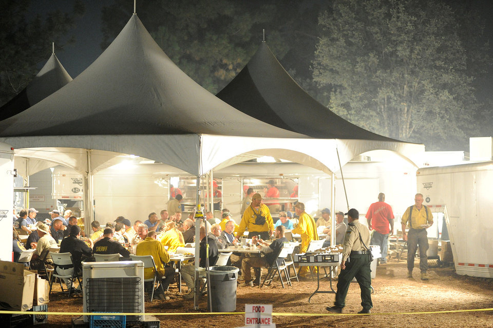 Photo - Firefighters chow under a series of tents set up at the Rim Fire incident command post 7 miles east of Groveland, after a long hard day of fighting the fire, which continues to conflagrate uncontrolled in the Stanislaus National Forest Saturday Aug. 24, 2013. (AP Photo/The Modesto Bee, Elias Funez) . NO SALES. NO MAGS. NO TV. ONLINE AP MEMBERS ONLY