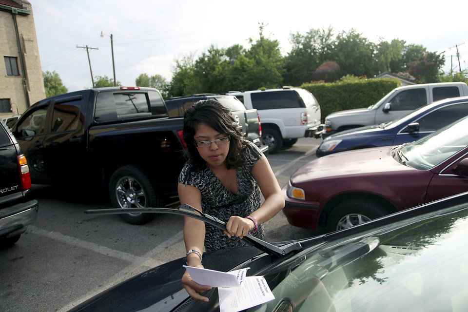 Tracey Medina puts fliers under windshield wipers in the parking lot at St. Francis Xavier Catholic Church in Tulsa. Photo by JOHN CLANTON, The Tulsa World