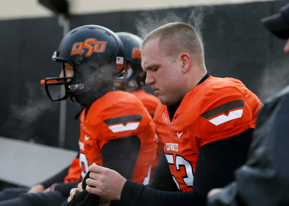 Photo - Steam rises from Oklahoma State's Andrew Suter (53) as the team gets ready for the Bedlam college football game between the Oklahoma State University Cowboys (OSU) and the University of Oklahoma Sooners (OU) at Boone Pickens Stadium in Stillwater, Okla., Saturday, Dec. 7, 2013. Photo by Bryan Terry, The Oklahoman