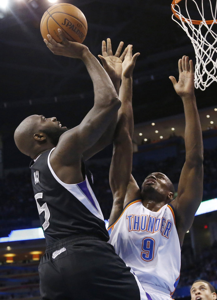 Photo - Sacramento Kings forward Quincy Acy (5) shoots in front of Oklahoma City Thunder forward Serge Ibaka (9) during the first quarter of an NBA basketball game in Oklahoma City, Friday, March 28, 2014. (AP Photo/Sue Ogrocki)