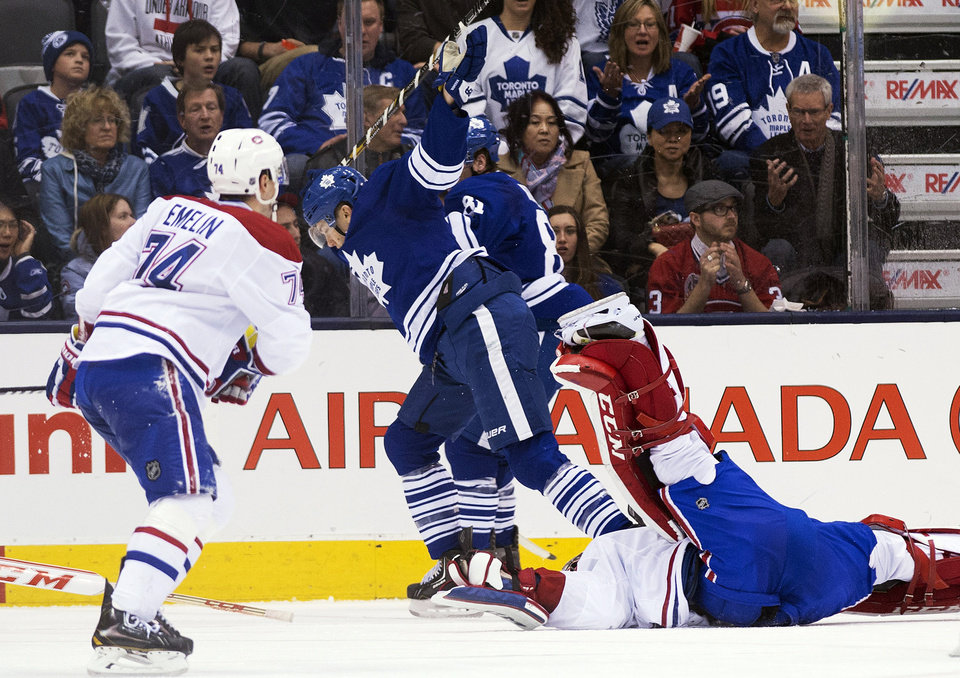 Photo - Toronto Maple Leafs forward James van Riemsdyk, center, gets called for an interference penalty after taking out Montreal Canadiens goalie Carey Price, right, during the third period of an NHL hockey game in Toronto on Saturday, March 22, 2014. (AP Photo/The Canadian Press, Nathan Denette)