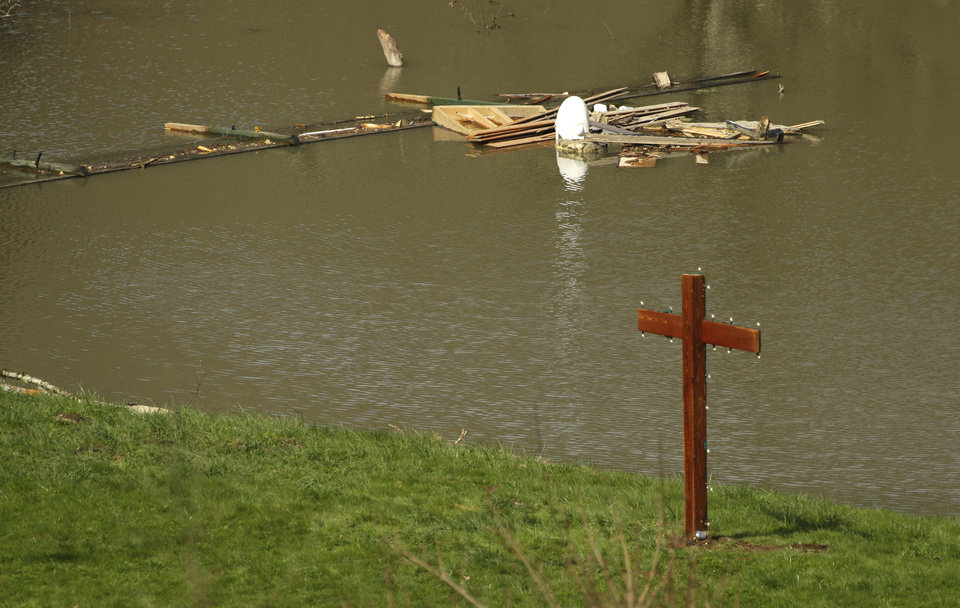 Photo - A newly constructed cross is shown Monday, March 31, 2014, at the edge of floodwaters next to the home of Don and Elaine Young near Darrington, Wash. The home sits just out of the debris field of the the massive mudslide that hit the nearby community of Oso,Wash. on March 22, 2014, but the property was affected by floodwaters from the baked up Stillaguamish River. (AP Photo/Ted S. Warren)