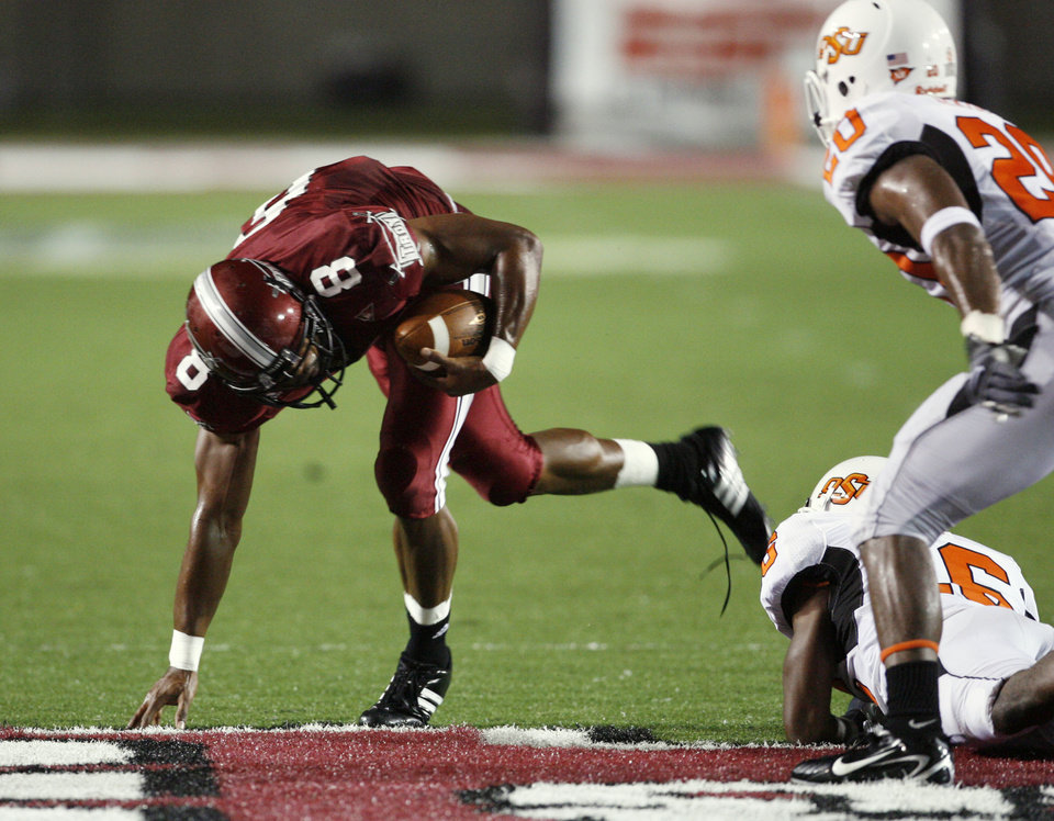 Gary Banks (8) slips a tackle attempt by Perrish Cox in first half action during the college football game between the Troy University Trojans and the Oklahoma State University Cowboys at Movie Gallery Veterans Stadium in Troy, Ala., Friday, September 14, 2007. BY STEVE SISNEY, THE OKLAHOMAN