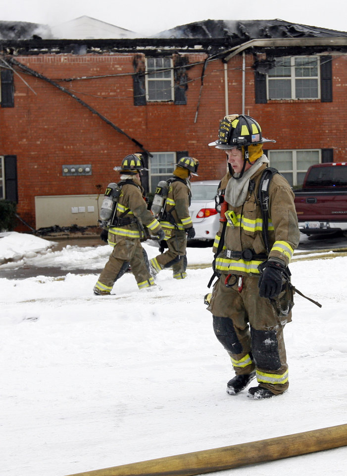Photo - Oklahoma City firefighters walk through snow after fighting a fire at the Tara Condominiums at NW 62 and Brookline Ave. in Oklahoma City, Thursday, Feb. 3, 2011. Photo by Nate Billings, The Oklahoman
