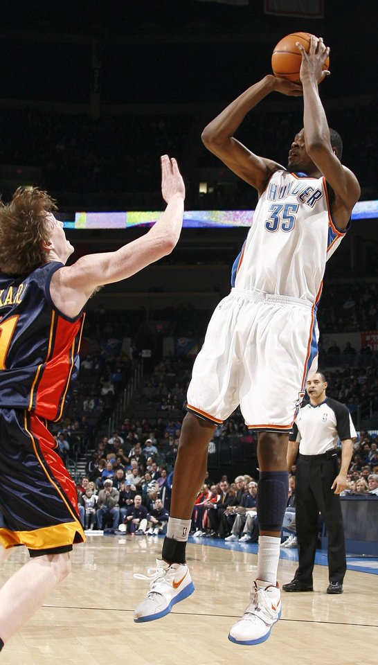 Photo - Oklahoma City's Kevin Durant (35) shoots over Golden State's Coby Karl (11) during the NBA game between the Oklahoma City Thunder and Golden State Warriors, Sunday, Jan.  31, 2010, at the Ford Center in Oklahoma City. Photo by Sarah Phipps, The Oklahoman