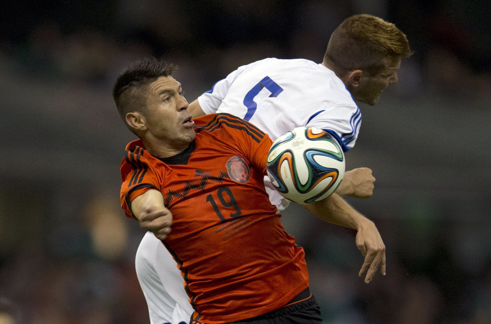 Photo - Israel's Rami Gershon, right, battles for the ball with Mexico's Oribe Peralta, during a friendly soccer match in Mexico City, Wednesday, May 28, 2014. (AP Photo/Eduardo Verdugo)