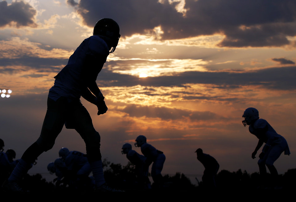 Photo -  Players are silhouetted at sunset Friday during a high school football scrimmage at Casady School in The Village. [Photos by Nate Billings, The Oklahoman]