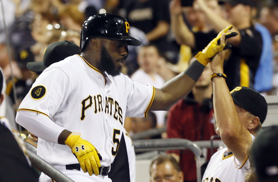 Photo - Pittsburgh Pirates' Josh Harrison (5) is greeted in the dugout by bench coach Jeff Banister after hitting a solo home run in the fifth inning of the baseball game against the St. Louis Cardinalson Tuesday, Aug. 26, 2014, in Pittsburgh. (AP Photo/Keith Srakocic)