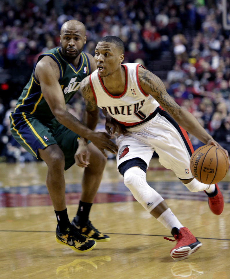 Photo - Portland Trail Blazers guard Damian Lillard, right, drives past Utah Jazz guard Jamaal Tinsley during the first quarter of an NBA basketball game in Portland, Ore., Saturday, Feb. 2, 2013. (AP Photo/Don Ryan)