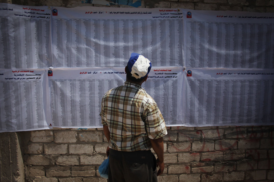Photo -   An Egyptian man searches for his name on a list of voters at a polling station in Alexandria, Egypt, Saturday, June 16, 2012. Egyptians voted Saturday in the country's landmark presidential runoff, choosing between Hosni Mubarak's ex-prime minister and an Islamist candidate from the Muslim Brotherhood after a race that has deeply polarized the nation. The two-day balloting will produce Egypt's first president since a popular uprising last year ousted Mubarak, who is now serving a life sentence. (AP Photo/Manu Brabo)