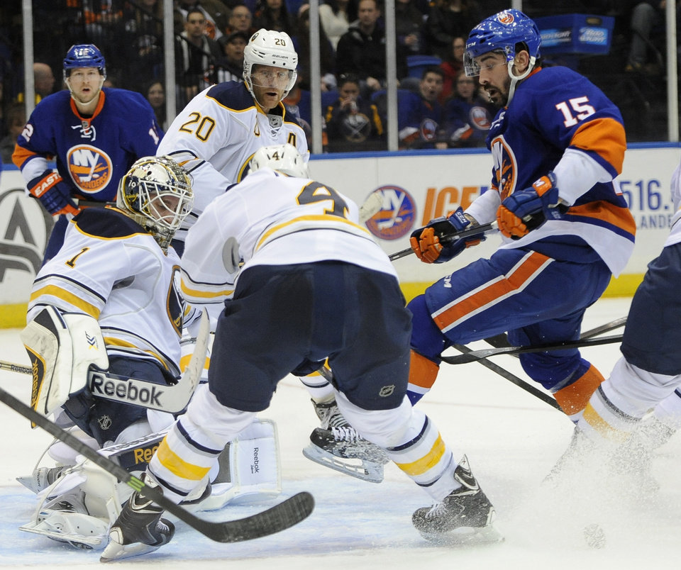 Photo - Buffalo Sabres goalie Jhonas Enroth (1) blocks a shot on goal by New York Islanders' Cal Clutterbuck (15) as Sabres' Henrik Tallinder (20) and Jamie McBain (4) defend in the second period of an NHL hockey game on Saturday, March 15, 2014, in Uniondale, N.Y. (AP Photo/Kathy Kmonicek)