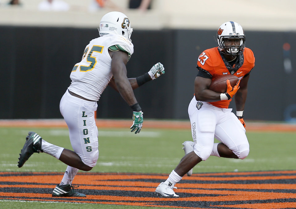 Photo - Oklahoma State's Rennie Childs (23) looks to get by Southeastern Louisiana's Abraham Freeman (25) during the college football game between the Oklahoma State Cowboys (OSU) and the Southeastern Louisiana Lions at Boone Pickens Stadium in Stillwater, Okla., Saturday, Sept. 12, 2015. Photo by Sarah Phipps, The Oklahoman