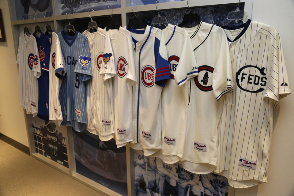 Photo - In this March 24, 2014, photo Chicago Cubs and the Chicago Feds jerseys worn over the past 100 years at Wrigley Field are on display at the Cubs offices in Chicago. The season long celebration of the 100th anniversary of the iconic ballpark begins with a visit from an old friend. Former Cubs first baseman Ryne Sandberg, now a manager, brings his Philadelphia Phillies to take on the Cubs in a baseball game on on opening day, Friday April 4, 2014 in Chicago. (AP Photo/M. Spencer Green)