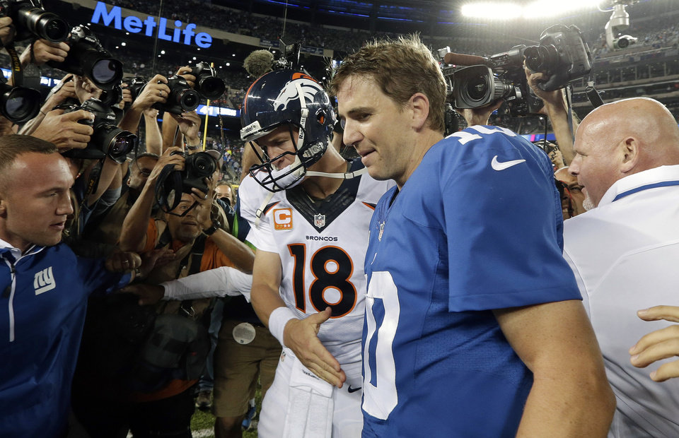 Photo - FILE - In this Sept. 15, 2013, file photo, Denver Broncos quarterback Peyton Manning (18) shakes hands with his brother New York Giants' quarterback Eli Manning (10) after an NFL football game  in East Rutherford, N.J. There is going to be a Manning in the Super Bowl, just not the one Eli Manning wanted.  (AP Photo/Frank Franklin II, File)
