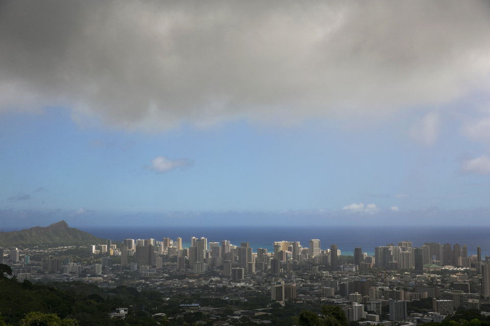 Photo - Clouds hang over Honolulu, seen from the top of Tanalus Drive on Thursday, Aug. 7, 2014. With Iselle, Hawaii is expected to take its first direct hurricane hit in 22 years. Tracking close behind it is Hurricane Julio. (AP Photo/Marco Garcia)