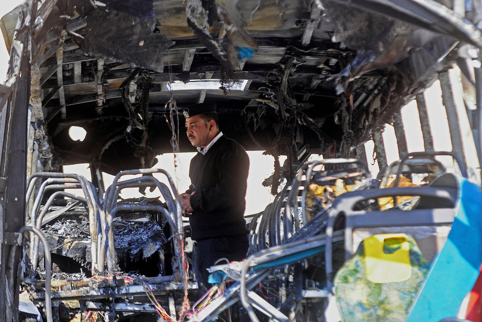 Photo - An Egyptian policeman inspects a damaged bus after a deadly explosion Sunday near the Egyptian border crossing with Israel in Taba, Egypt, Monday, Feb. 17, 2014. An explosion tore through a bus filled with South Korean sightseers in the Sinai Peninsula on Sunday, killing at least four people and raising fears that Islamic militants have renewed a bloody campaign to wreck Egypt's tourism industry. (AP Photo/Nameer Galal)