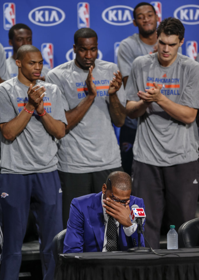 Photo - Oklahoma City's Kevin Durant wipes the tears from his eyes as teammates Russell Westbrook, Kendrick Perkins, Steven Adams and the rest of the team applaud during a news conference announcing Durant as the winner of the 2013-14 Kia NBA Basketball Most Value Player Award in Oklahoma City, Okla. on Tuesday, May 6, 2014. Photo by Chris Landsberger, The Oklahoman