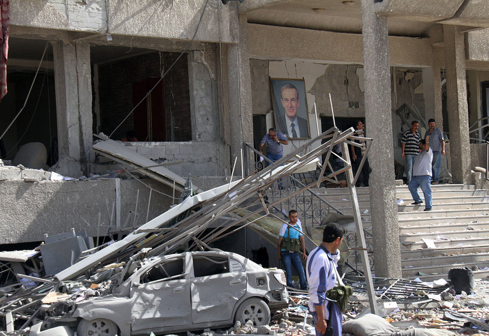 Photo - Syrian security officers stand next to a portrait of late Syrian President Hafez Assad at the entrance of a damaged military intelligence building where two bombs exploded, at Qazaz neighborhood in Damascus, Syria, on Thursday May 10, 2012. Two strong explosions ripped through the Syrian capital Thursday, killing or wounding dozens of people and leaving scenes of carnage in the streets in an assault against a center of government power. (AP Photo/Bassem Tellawi) ORG XMIT: BEI118