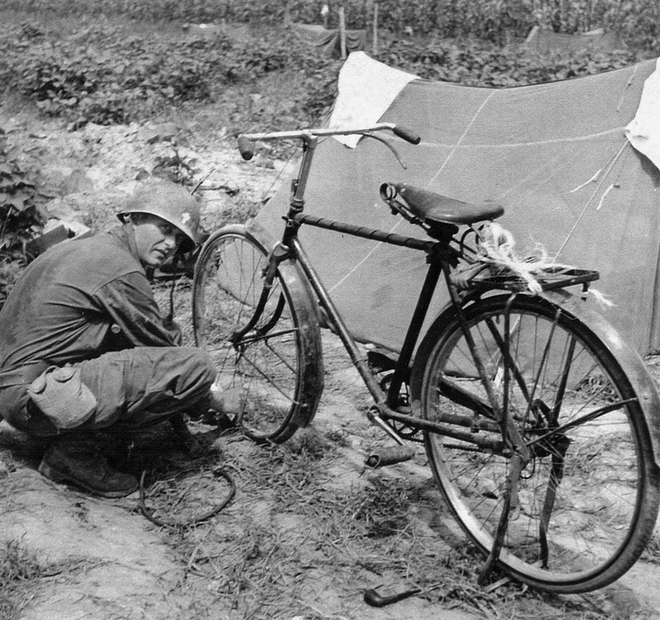 Photo - In this Aug. 11, 1950 photo provided by Col. Raymond A. Skeehan via the U.S. Army, the Rev. Emil Kapaun repairs his bicycle in Korea. Kapaun died in a prisoner of war camp on May 23, 1951, his body wracked by pneumonia and dysentery. Soldiers who knew him never forgot the plain-spoken, pipe-smoking, bike-riding chaplain who urged them to keep their spirits up. On April 11, 2013, President Barack Obama will award the legendary chaplain the Medal of Honor posthumously. (AP Photo/Col. Raymond A. Skeehan via the U.S. Army)