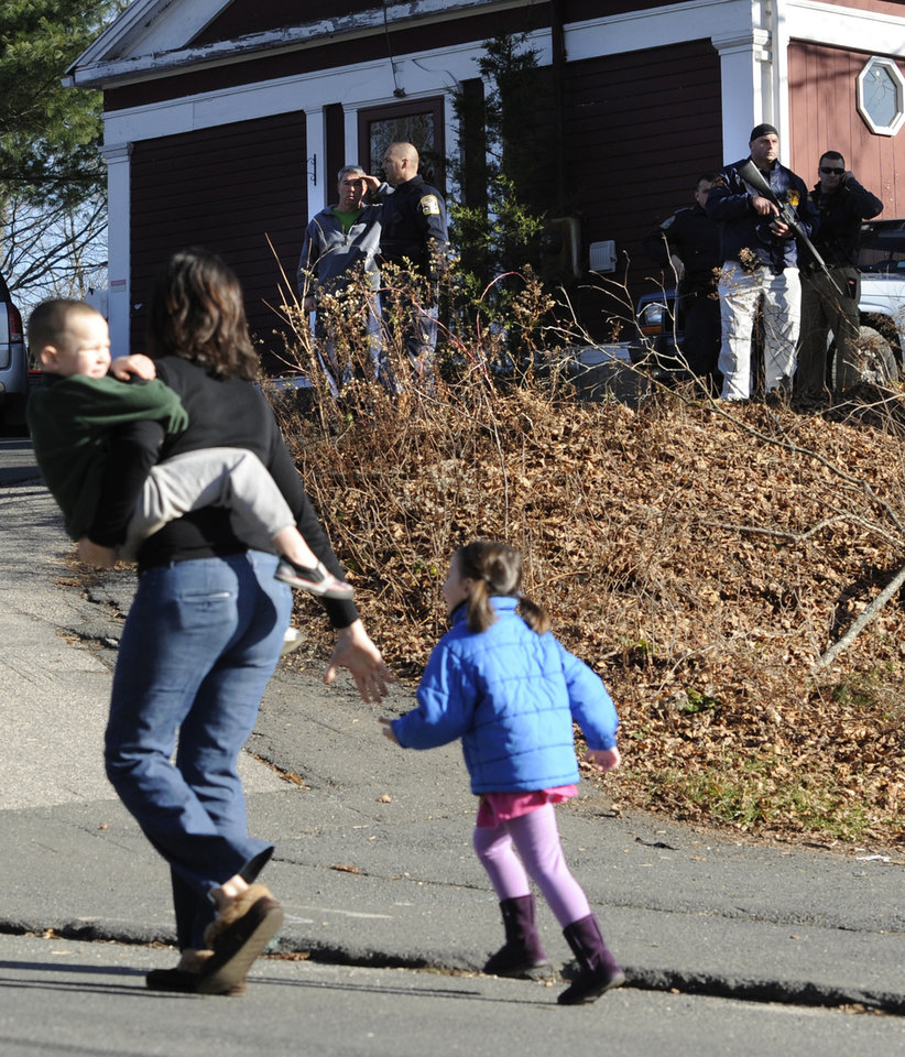 Photo - A mother runs with her children as police above canvass homes in the area following a shooting at the Sandy Hook Elementary School in Newtown, Conn., about 60 miles (96 kilometers) northeast of New York City, Friday, Dec. 14, 2012. An official with knowledge of Friday's shooting said 27 people were dead, including 18 children. (AP Photo/Jessica Hill)