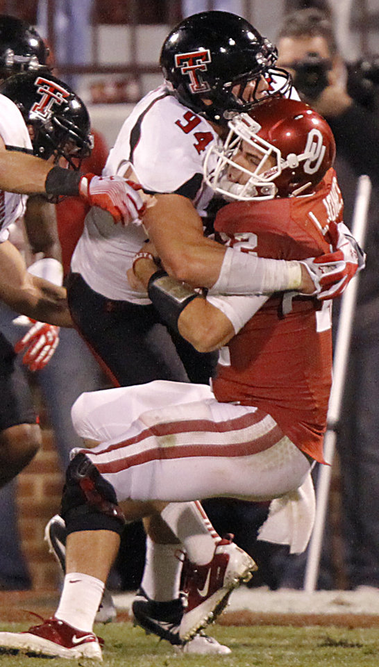 Photo - Texas Tech's Scott Smith (94) hits Oklahoma's Landry Jones (12) during the college football game between the University of Oklahoma Sooners (OU) and Texas Tech University Red Raiders (TTU) at the Gaylord Family-Oklahoma Memorial Stadium on Saturday, Oct. 22, 2011. in Norman, Okla. Photo by Chris Landsberger, The Oklahoman