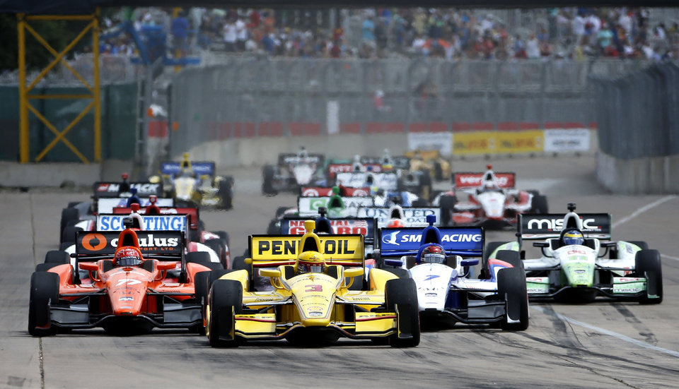 Photo - Helio Castroneves (3), of Brazil, leads the pack from the pole position at the start of the second IndyCar Grand Prix of Houston auto race Sunday, June 29, 2014, in Houston. (AP Photo/David J. Phillip)