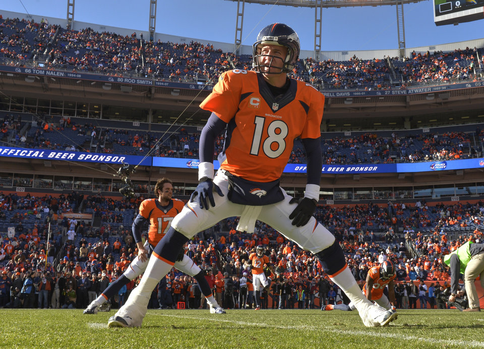 Photo - Denver Broncos quarterback Peyton Manning (18) stretches before playing against the San Diego Chargers in an NFL AFC division playoff football game, Sunday, Jan. 12, 2014, in Denver. (AP Photo/Jack Dempsey)